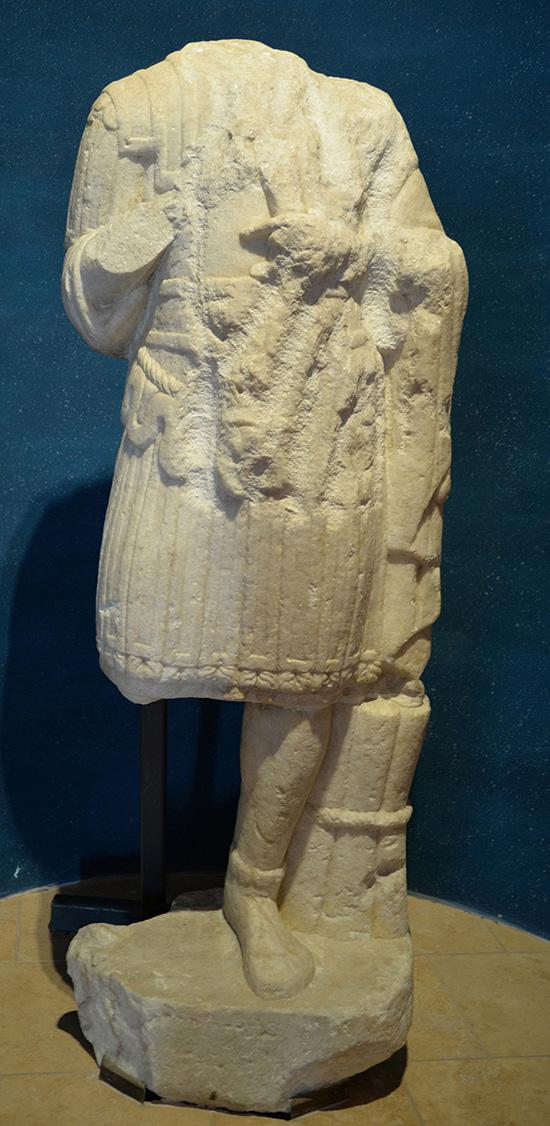 Staty i marmor från ca 100- eller 200-talet e.Kr. Den föreställer en högt uppsatt man i paraduniform. Statyn stod en i gång i den södra delen av militärstaden i Aquincum.